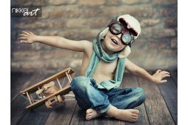 Small boy playing with a plane on wooden floor