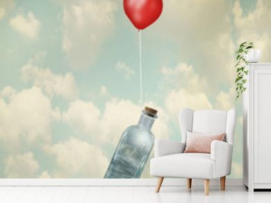 Surreal image representing a glass bottle with a stormy sea inside carried by a red balloon flying in the clouds