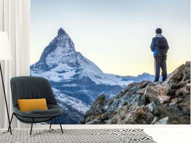 Junger Mann beim Bergsteigen in den Schweizer Alpen mit Matterhorn im Hintergrund