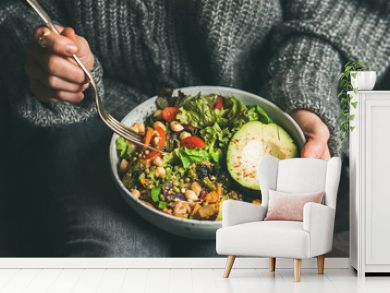 Healthy vegetarian dinner. Woman in jeans and warm sweater holding bowl with fresh salad, avocado, grains, beans, roasted vegetables, close-up. Superfood, clean eating, vegan, dieting food concept