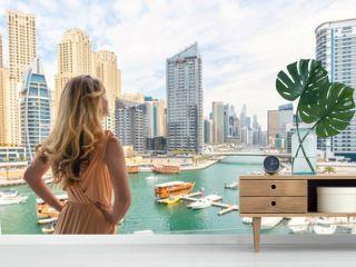 Woman in Dubai Marina, United Arab Emirates. Attractive lady wearing a long dress admiring Marina daylight views