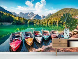 Six pleasure boats on Fusine lake. Bright morning scene of Julian Alps with Mangart peak on background, Province of Udine, Italy, Europe. Traveling concept background.