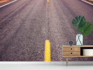 Asphalt road in Badlands National Park, focus on yellow lane, travel concept, color toning applied, USA.