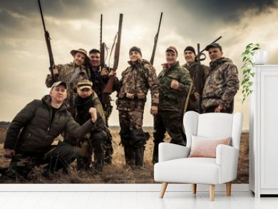 Hunters standing together against sunrise sky in rural field during hunting season. Concept for teamwork.