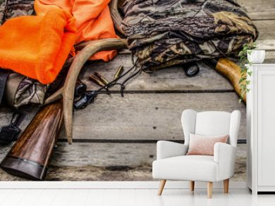 Deer Hunting Background. Hunting rifles, scope, antlers, bullets, and hunting apparel on a rustic wooden background with copy space.