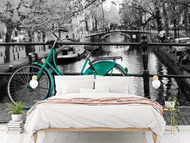 A picture of a lonely blue green bike on the bridge over the channel in Amsterdam. The background is black and white.