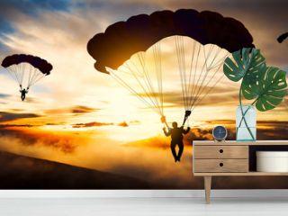 Silhouette parachutist landing at sunset