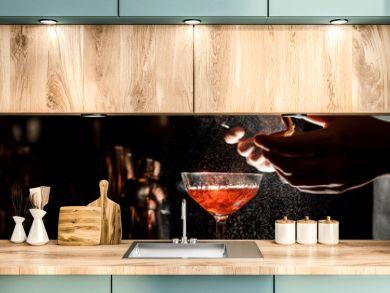 Bartender sprays an orange peel in cocktail glass