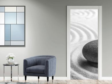 Grey stone on sand with pattern, space for text. Zen, meditation, harmony