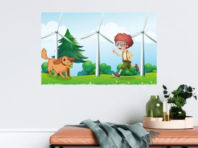 A boy playing with his dog near the windmill