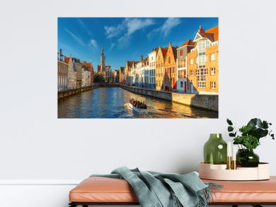 Tourist boat on canal Spiegelrei and Jan Van Eyck Square in the morning in Bruges, Belgium