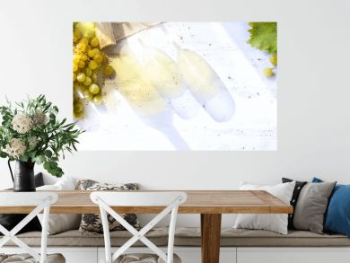 grapes on white table; seasoning vineyard background; Bottle and glasses