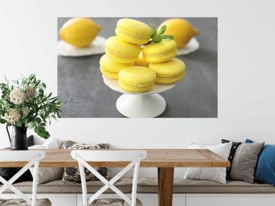 Dessert stand with tasty homemade lemon macarons on table