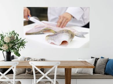 A large zander fish fillet lying on a white chopping board. A chef filleting a fish in the background.