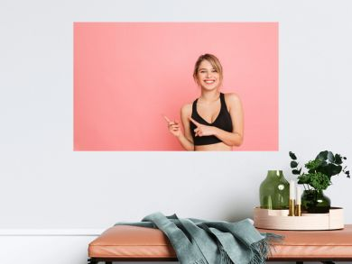 Young sports blonde woman make fitness exercises isolated posing pointing.