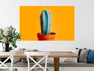 Green cactus in decor pot over bright orange pastel background. Colorful yellow summer trendy creative concept.