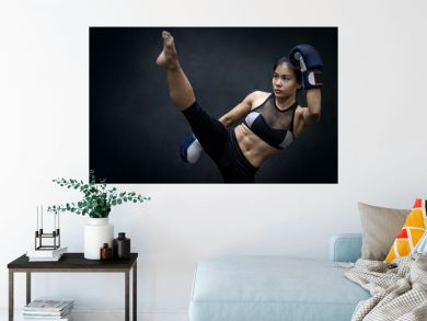 Young Asian woman boxer with blue boxing gloves kicking in the exercise gym, Martial arts on black background. Female boxing class concept