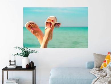 Upside woman feet and red pedicure wearing pink sandals, sunglasses at seaside. Funny and happy fashion young woman relax on vacation. Chill out girl at beach. Creative for tour agent. Weekend travel.