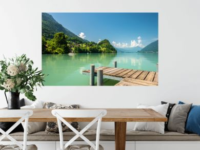View of Brienz lake with clear turquoise water. Wooden pier. Traditional wooden houses on the shore of Brienz lake in the village of Iseltwald, Switzerland