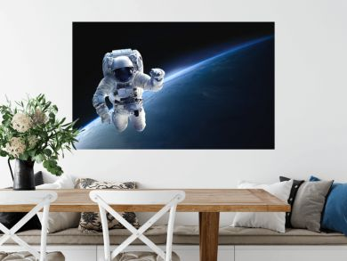 Astronaut in the outer space over the planet Earth. Abstract wallpaper. Spaceman. Black bakground. Elements of this image furnished by NASA