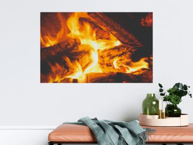 Closeup toned image of fire flames covering burning wooden logs in the fireplace at house
