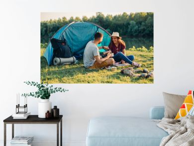 friends on camping outdoor by the lake or river