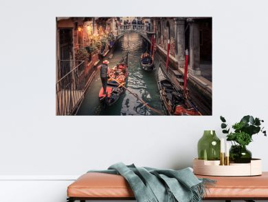 Gondolier rowing down a narrow canal in venice with christmas lights illuminating his gondola