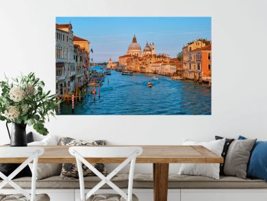 Panorama of Venice Grand Canal with gondola boats and Santa Maria della Salute church on sunset from Ponte dell'Accademia bridge. Venice, Italy
