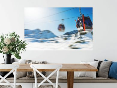 ski lift gondolas against blue sky over snowy mountains at ski resort at Italy Alps on sunny winter day. banner copy space