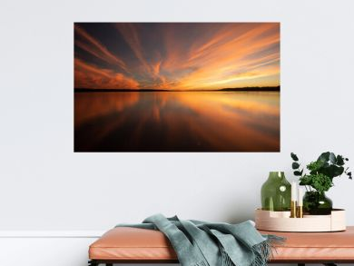Colorful Golden and Orange Sunset Sky Over River With Reflections in the Calm Water