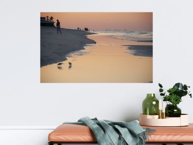 Breathtaking scenery of a beach during the golden hour with pink hues reflected on water