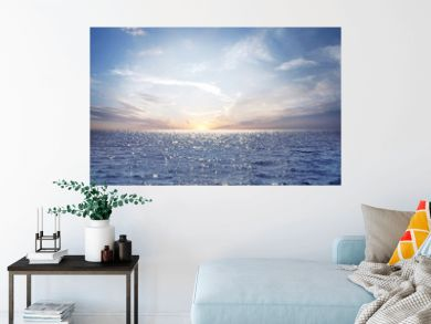 Rising sun on the horizon above a calm ocean or sea. On the blue sky white clouds