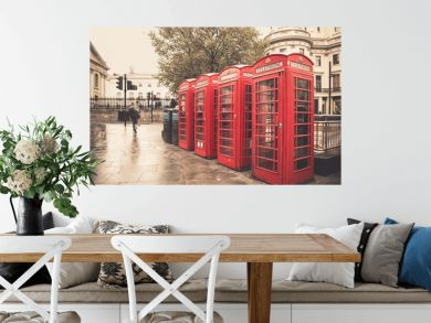 Vintage style  red telephone booths on rainy street in London