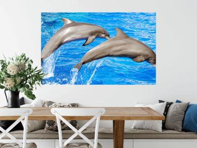 Two dolphins jumping in clear blue sea.