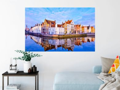 Cityscape view of Bruges and traditional houses reflected in water at sunrise in Belgium