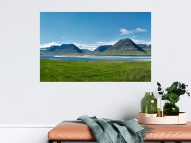 Travel to Iceland. beautiful sunrise over the ocean and fjord in Iceland. Icelandic landscape with mountains, blue sky and green grass on the foreground. View of the road to houses in the north-west