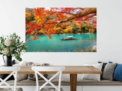 Boatman punting the boat at river. Arashiyama in autumn season along the river in Kyoto, Japan.