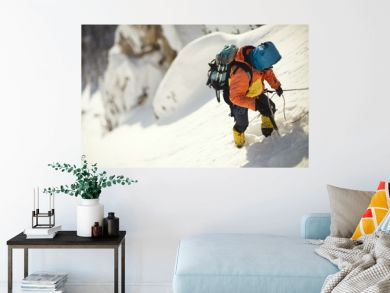 Mountaineer clinging to a rope on a steep snow-covered mountain slope.  Tilt-shift effect.