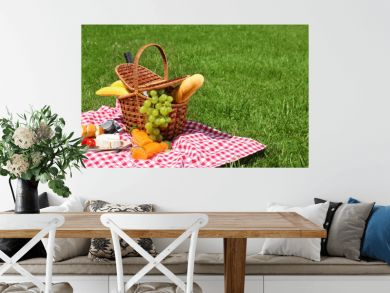 Basket with food on blanket prepared for picnic in park