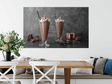 Glasses with chocolate milk shakes on grey table