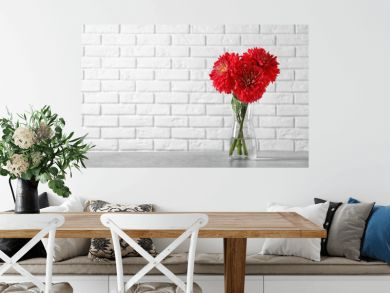 Beautiful dahlia flowers in glass vase on table against brick wall. Space for text