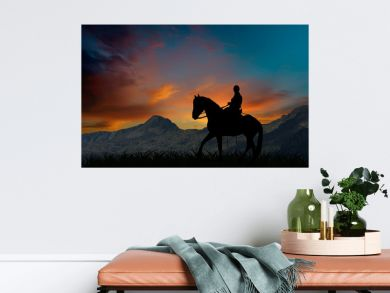 Silhouette of a horseman riding on horseback at sunset by mountains
