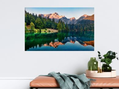 Calm morning view of Fusine lake. Colorful summer sunrise in Julian Alps with Mangart peak on background, Province of Udine, Italy, Europe. Beauty of nature concept background.