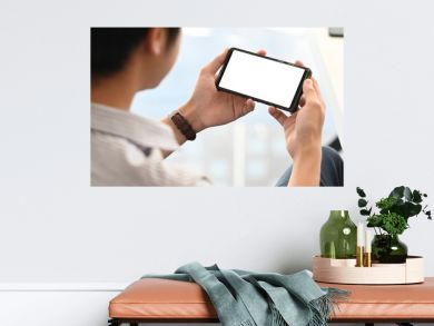 Creative man relaxing/watching a movie from cropped black smartphone with white blank screen at the modern working table as background. Relaxing after finished work concept.