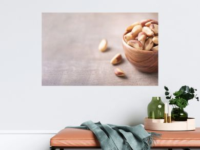 Brazil nuts in wooden bowl on wood textured background. Copy space. Superfood, vegan, vegetarian food concept. Macro of brazil nut texture, selective focus. Healthy snack.