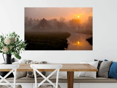 Morning sunrise sun reflected on a foggy Dutch traditional green wooden houses in the rural area of the Netherlands