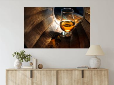 A glass of whiskey in oak barrels