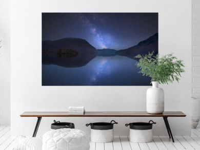 Vibrant Milky Way composite image over landscape of Crummock Water in Lake District England