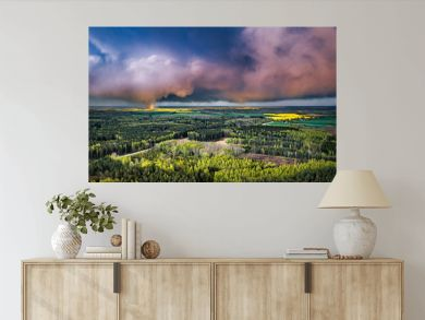 Aerial landscape of countryside with colorful storm clouds. Extreme thunderstorm over a pine forest and road.