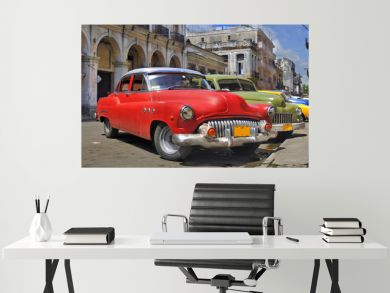 Havana street with colorful old cars in a raw